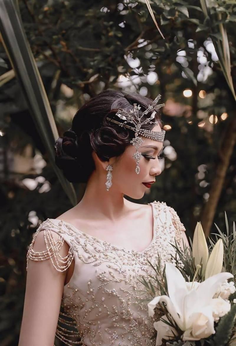 Hairpiece, makeup dan gaun yang mendukung tema 1920