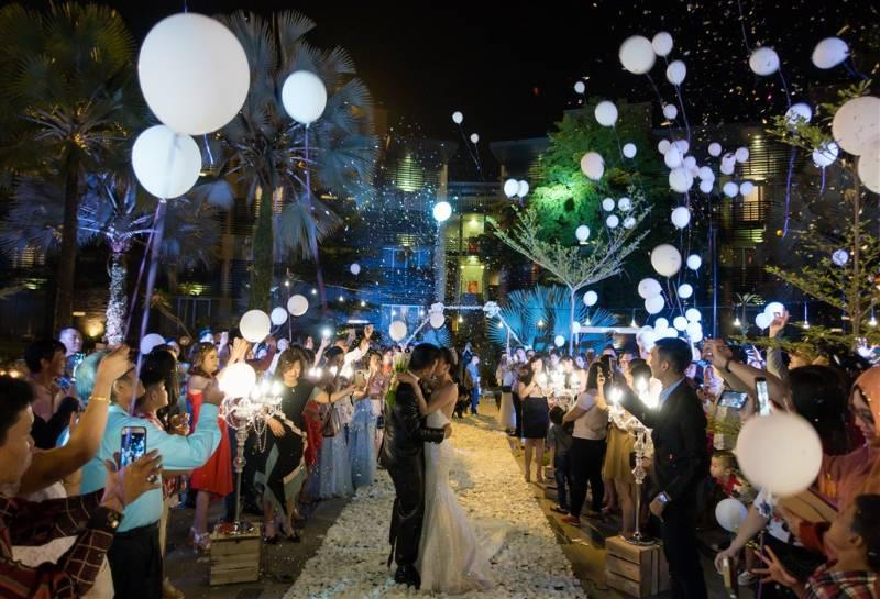 Wedding kiss romantis disaksikan para tamu dan balon putih
