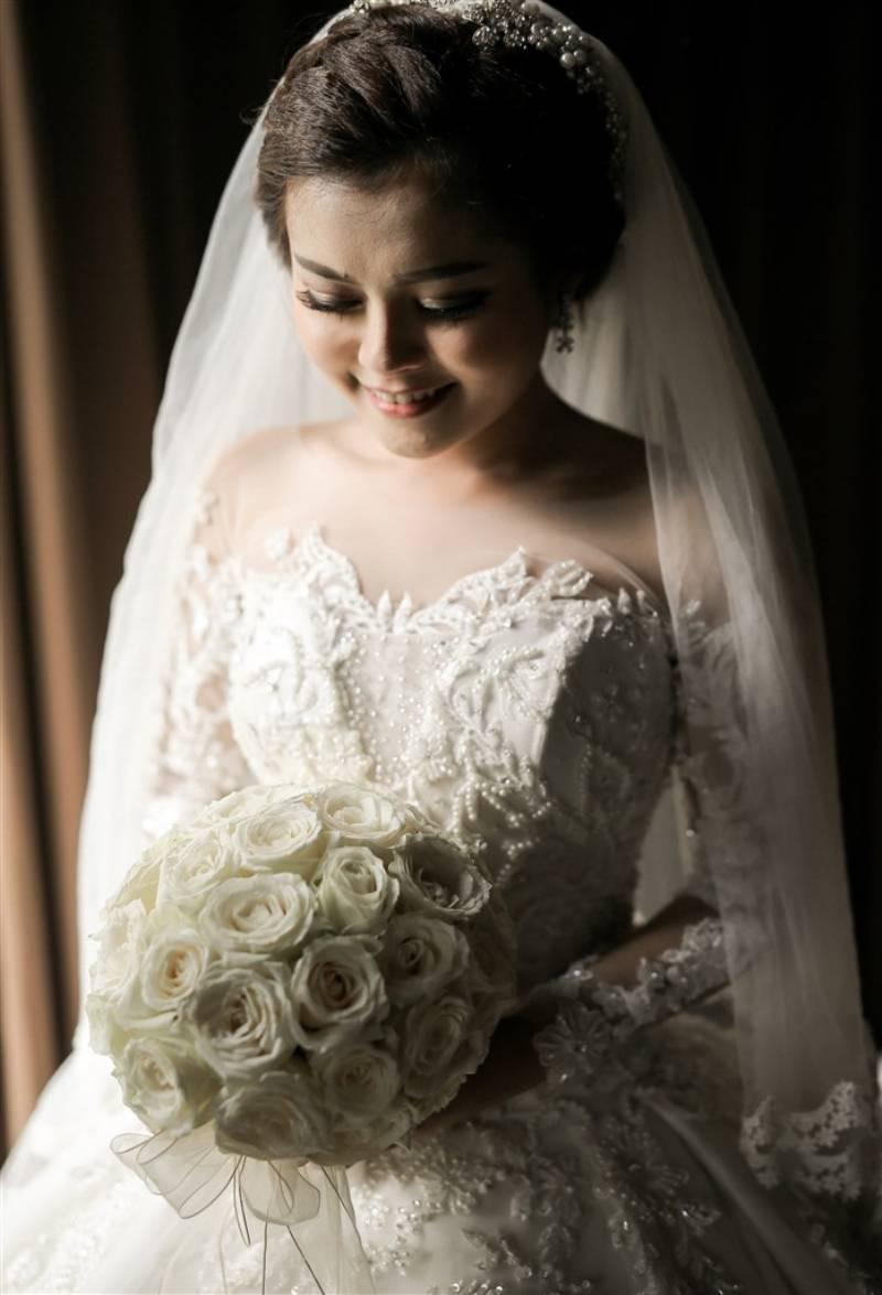 Hand bouquet putih sewarna dengan gaun yang dipakai