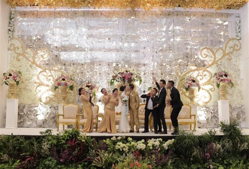 Kecup sayang yang disaksikan bridesmaid dan groomsmen