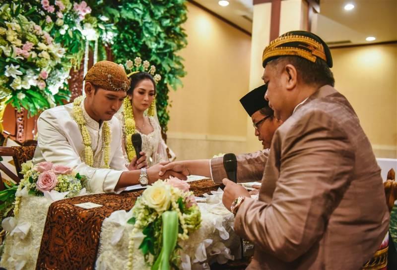 Adit menjabat tangan penghulu yang sering membuat gugup setiap pengantin pria