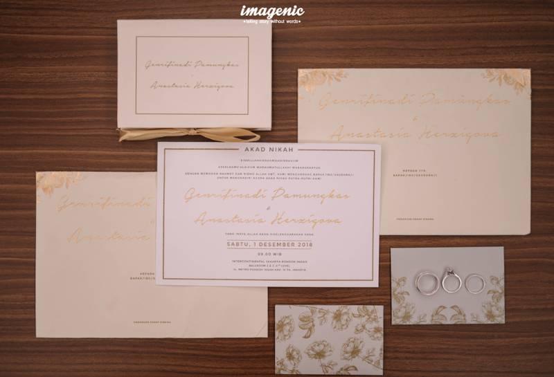 Kartu undangan cantik berdampingan dengan cincin kawin
