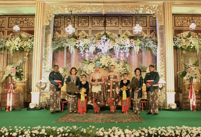 Pasangan pengantin yang berbahagia bersama kedua pasang orang tua